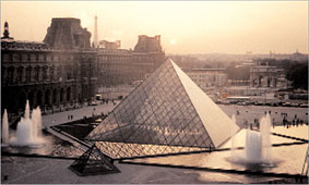 [Photo of the large glass pyramid of le Musee du Louvre]